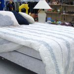Bed box spring and mattress with pillows and sheets.