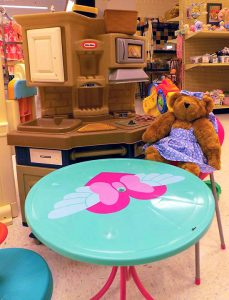 Plush Bear sitting at kids table with a play kitchen set.