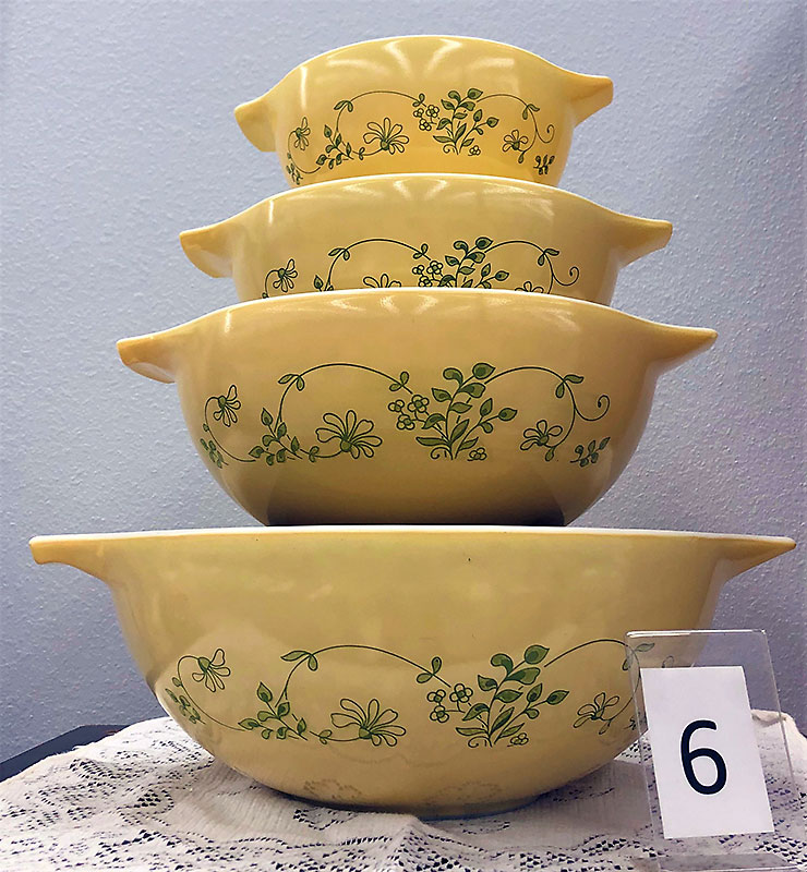 Yellow Pyrex bowls with green floral pattern.