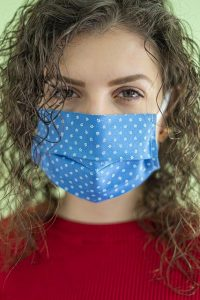 Woman wearing surgical mask while shopping.