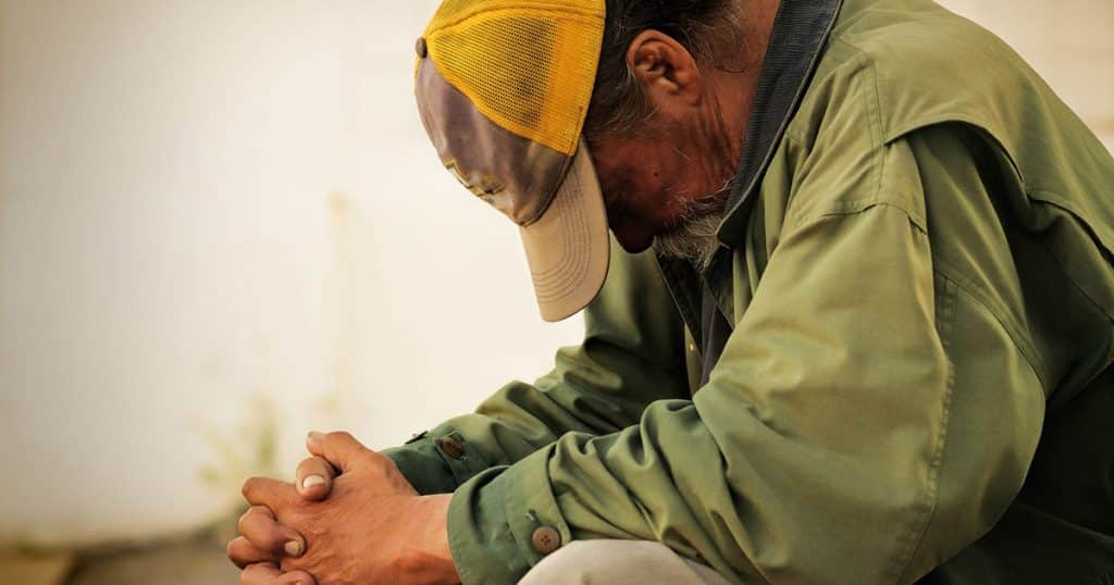 Homeless person praying. Homeless shelter post.